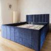 Łóżko tapicerowane granatowym aksamitem Florencja, mebel na wymiar zgodnie z projektem klienta. Pojedyncze panele na zagłówku, pionowe przeszycia na ramie.