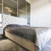 Łóżko tapicerowane w stylu glamour Charlotte, tkanina połyskujący aksamit Prime 900 w kolorze beżu. Ramę łóżka i zagłówek zdobi pikowanie.