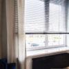Żaluzje aluminiowe perforowane w gabinecie w kolorze grafitowym. Pozwalają na rozproszenie promieni słonecznych i zasłonięcie pomieszczenia.