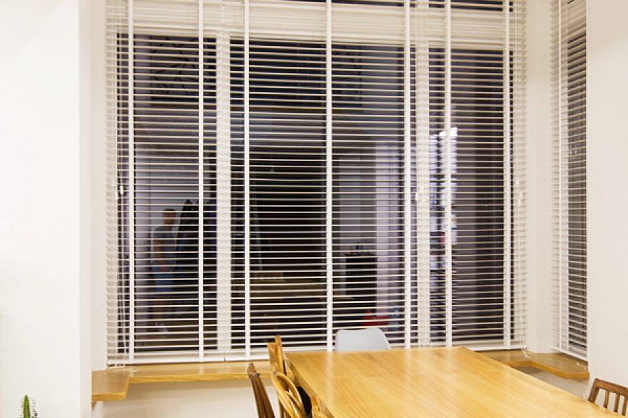 Białe żaluzje drewniane 50mm z taśmą. Montowane we wnęce okiennej. Szerokie lamele żaluzji drewnianych z taśmą drabinkową wykonywane na wymiar.