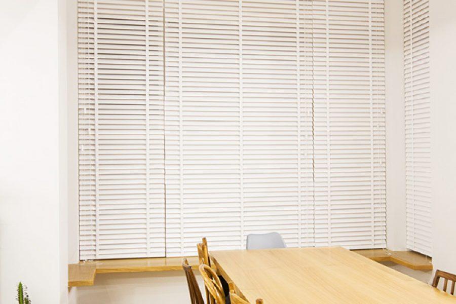 Białe żaluzje drewniane 50mm z taśmą. Montowane we wnęce okiennej.