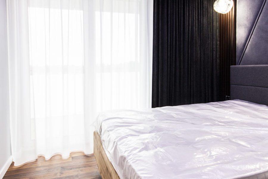 Zasłony w sypialni czarny aksamit, tkanina Cameron o przecieranej, połyskującej strukturze. Zasłony na flexach marszczenie 200%. Karnisz sufitowy KS ukryty we wnęce sufitowej. Zasłony zebrane na jedną stronę.