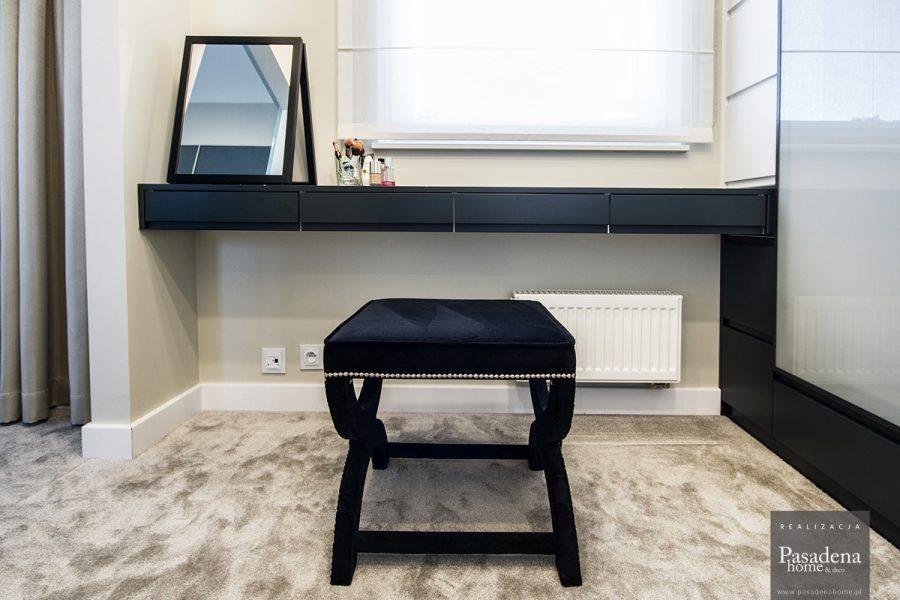 Pufa tapicerowana w stylu glamour Chicago. Tapicerowany czarną tkaniną welurową. Gięty kształt nóg i siedzisko zdobione są srebrną taśmą pineskową.