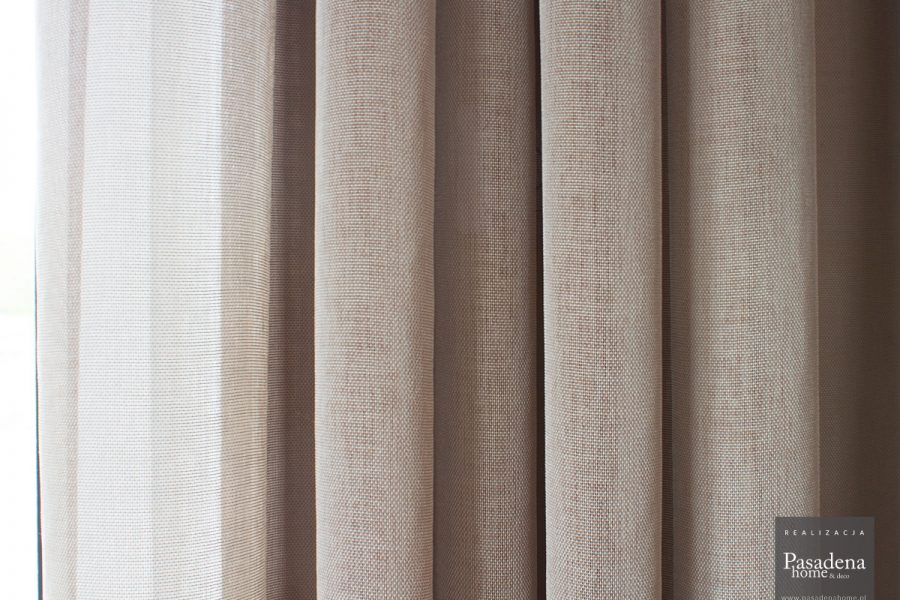 Lekka firana siatka w salonie z beżowej tkaniny Viva 10. Zwiewny materiał nadaje lekkości pomieszczeniu i służy jako firano - zasłona. Delikatna, mocno przezierna struktura o subtelnym połysku