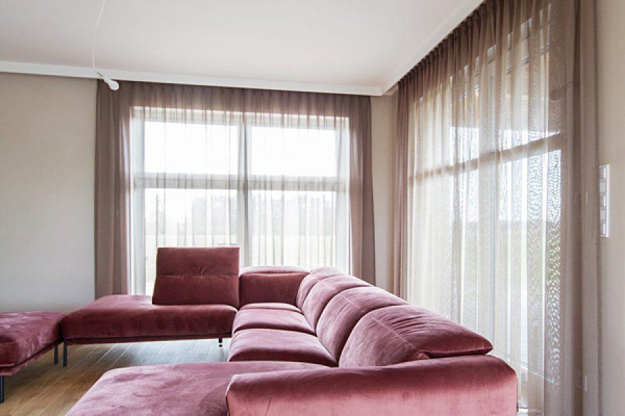 Lekka firana siatka w salonie z beżowej tkaniny Viva 10. Zwiewny materiał nadaje lekkości pomieszczeniu i służy jako firano - zasłona. Delikatna, mocno przezierna struktura o subtelnym połysku. Marszczenie 200%, szycie flex.