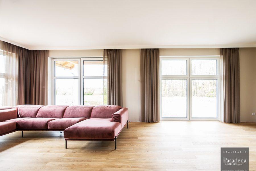 Lekka firana siatka w salonie z beżowej tkaniny Viva 10. Zwiewny materiał nadaje lekkości pomieszczeniu i służy jako firano - zasłona. Delikatna, mocno przezierna struktura o subtelnym połysku. Montaż na karniszu sufitowym Forest KS.