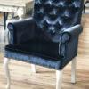 Krzesło tapicerowane w stylu glamour Emanuel dom Białystok. Zdobione kołatką i taśmą pineskowa w aksamitnej tkaninie obiciowej Fancy z wysokim połyskiem. Pikowane oparcie z guzikami i nogi w stylu ludwik w kolorze białym.