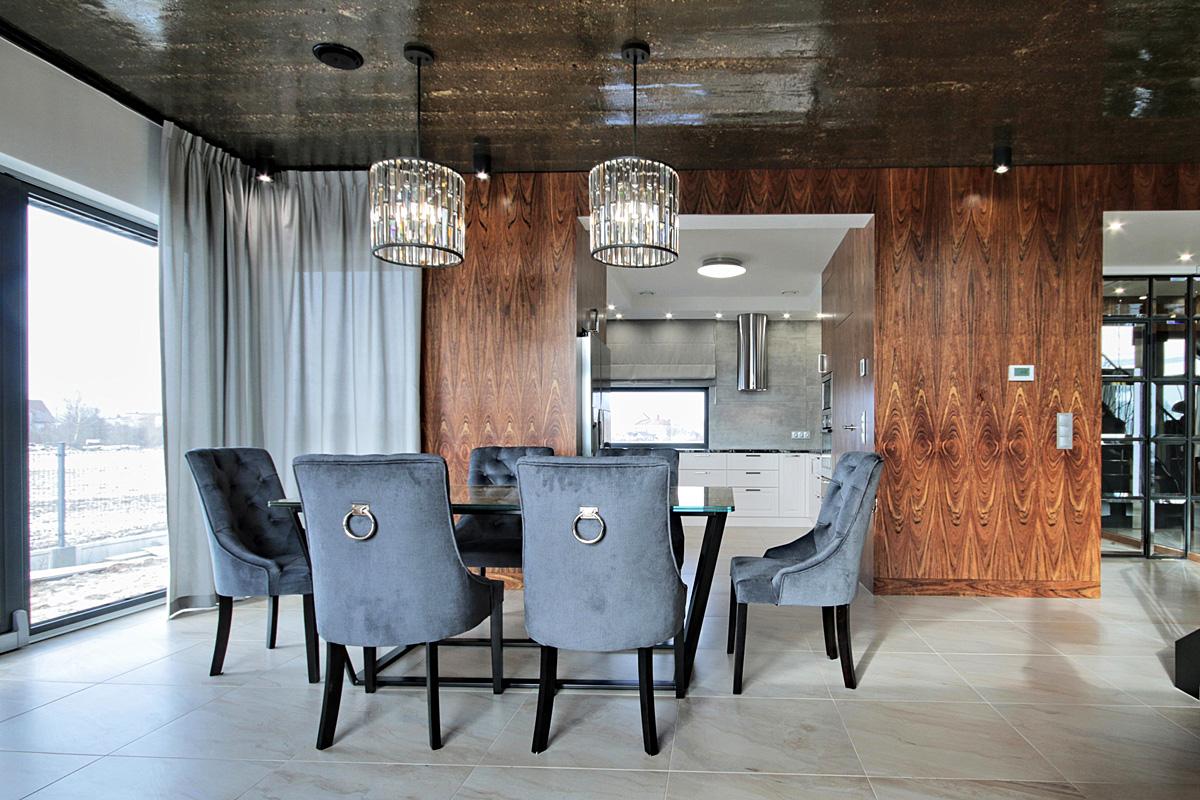 Krzesło tapicerowane Lady Chesterfield w stylu nowojorskim tapicerowane w tkaninie Novel, wykończone dekoracyjną kołatką w kolorze srebrnym. Projekt architekt Tomasz Czajkowski.