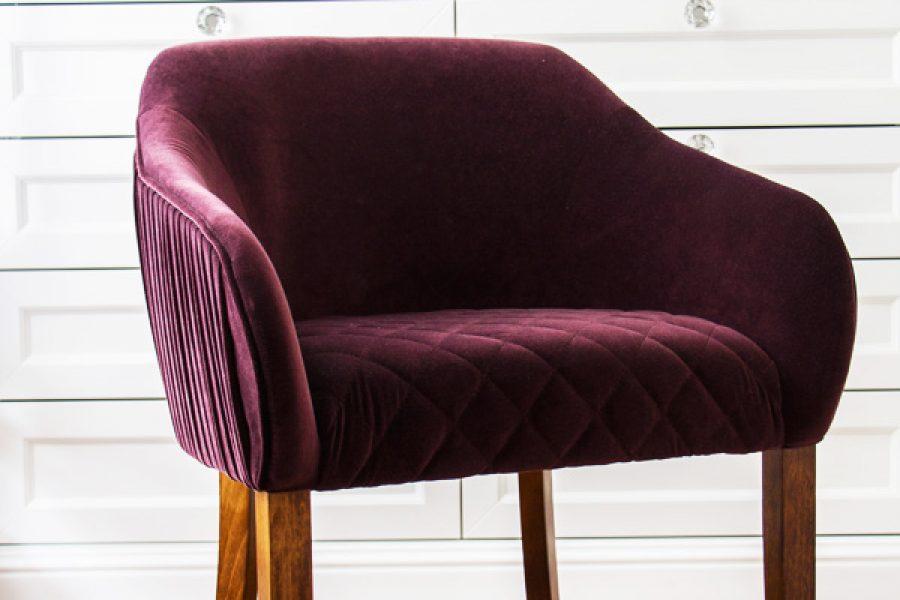 Krzesło tapicerowane styl glamour Coco apartament Warszawa. Krzesło z podłokietnikami w tkaninie obiciowej Glam Velvet, grubym aksamicie. Na boczkach krzesła dekoracyjne zakładki, siedzisko pikowane w karo.