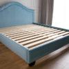 Łóżko tapicerowane styl nowojorski Henderson dom Białystok. Tapicerowane aksamitną tkaniną obiciową King Velvet w jasno niebieskim kolorze, zagłówek tapicerowany falisty wykończony dwiema subtelnymi lamówkami.