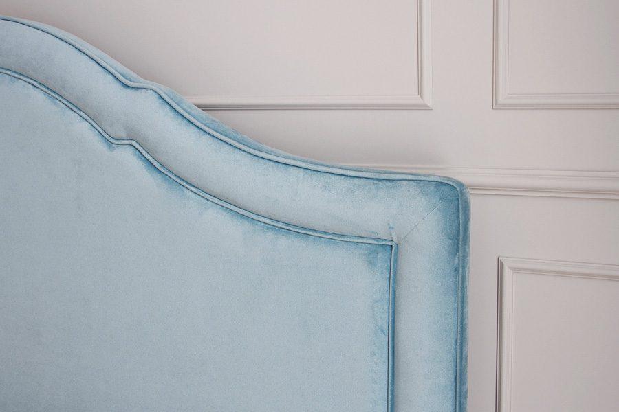 Łóżko tapicerowane styl nowojorski Henderson dom Białystok. Zagłówek tapicerowany falisty wykończony dwiema subtelnymi lamówkami.