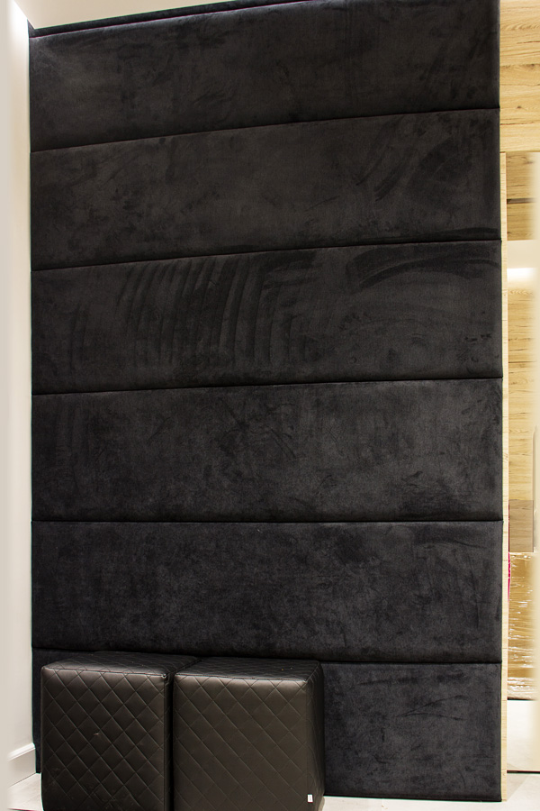 Ściana tapicerowana w przedpokoju dom Białystok. Panele tapicerowane wykonane przyjemnej w dotyku, łatwoczyszczącej z tkaniny obiciowej Milton, pianka o grubości 3cm.
