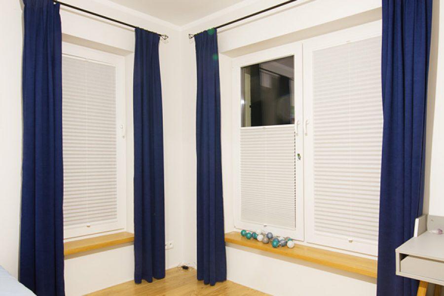 Plisy i zasłony w pokoju dziecka. Granatowe zasłony z welurowej tkaniny Deserto 31 uszyte na flexach i montowane na karniszu drążkowym. Plisy montowane w ramie okiennej z przeziernej tkaniny C1701.