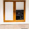 Rolety plisowane na wymiar montowane w drewnianej ramie okiennej. Plisy okienne z białej tkaniny, lekko transparentnej.