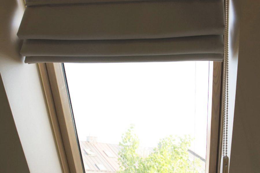 Roleta rzymska na oknie dachowym mieszkanie Białystok. Tkanina zaciemniająca dimout Mami Mix we wzór małej jodełki z subtelnym połyskiem. Mechanizm mocowany we wnęce okiennej. Projekt architekt Joanna Karwowska.