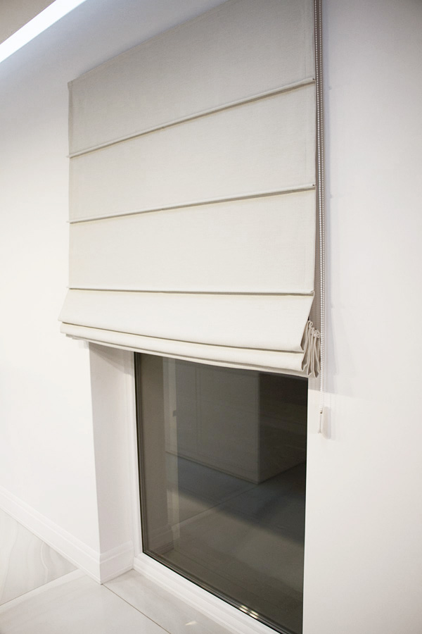 Roleta rzymska zaciemniająca na oknie balkonowym dom Białystok. Tkanina zaciemniająca Mami Mix z wzorem jodełki i delikatnym połyskiem. Montowana 20 cm nad wnęką okienną.
