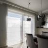 Dwie rolety rzymskie w salonie na wymiar, z tkaniny Larkin w kolorze złamanej bieli. Montaż do sufitu, rolety rzymskie na oknie balkonowym.