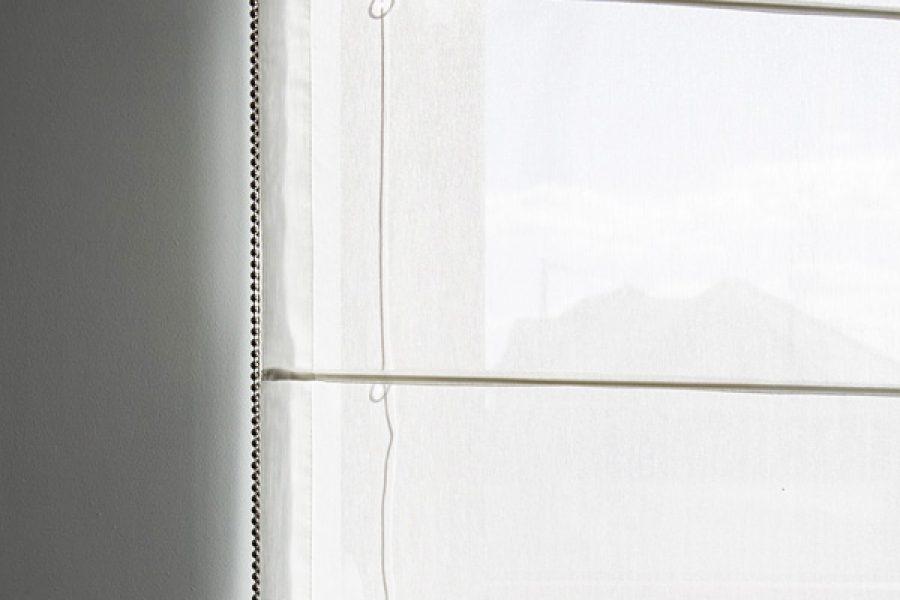 Rolety rzymskie w kuchni okno narożne z tkaniny Larkin złamana biel. Montaż do podwieszanego sufitu. Dwie rolety z białej prześwitującej tkaniny firanowej.