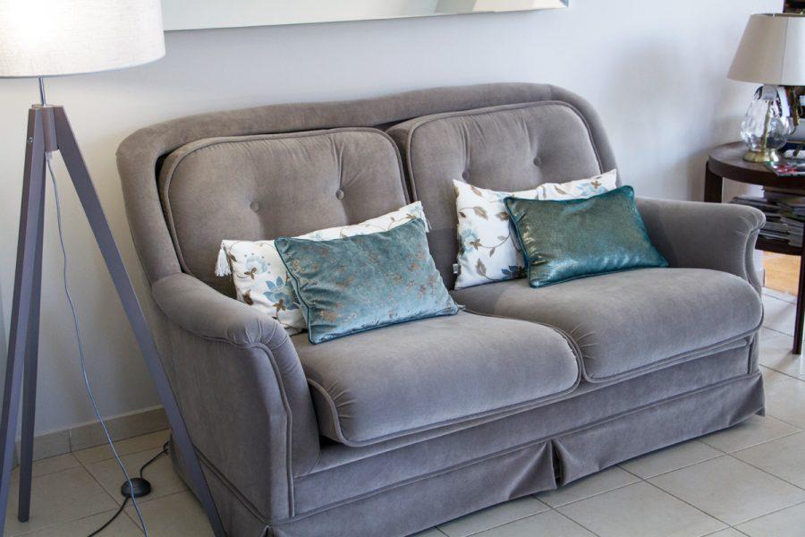 Sofa tapicerowana w tkaninie obiciowej Glam Velvet dom Białystok. Gruby i łatwoczyszczący aksamit z dekoracyjnymi poduszkami z ekskluzywnych tkanin z haftem i aksamitu z nabłyszczaną strukturą w kolorze miedzi.