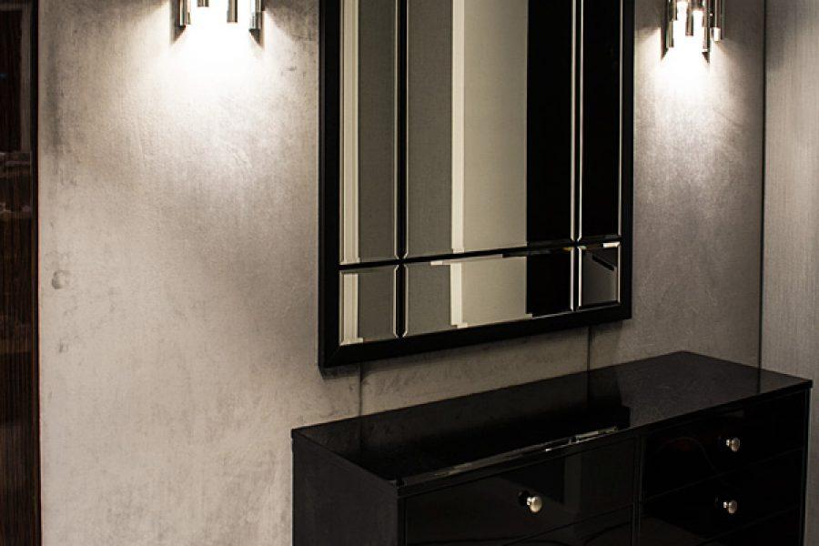 Ściana tapicerowana w korytarzu mieszkanie Białystok. Panele tapicerowanie tkaniną Art Velvet podświetlają kinkiety Fushion. Połyskujący materiał welurowy ociepla eleganckie wnętrze.
