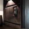 Panele tapicerowane w przedpokoju montowane na rzepy z łatwym dostępem serwisowym do skrzynki teletechnicznej.