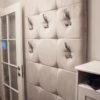 Panele tapicerowany w przedpokoju z wieszakami na ubrania Białystok. Przytulna tkanina o grubej strukturze polaru, pisząca się w kolorze szarym.