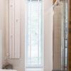 Żaluzje aluminiowe 50mm białe na wymiar w łazience. Szeroka żaluzja montowana jest we wnęce okiennej na uchwycie sufitowym.